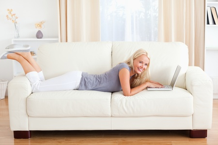 attractive couch: Woman lying on a sofa with a notebook in their living room Stock Photo