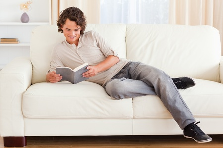 Man reading a book in his living room photo