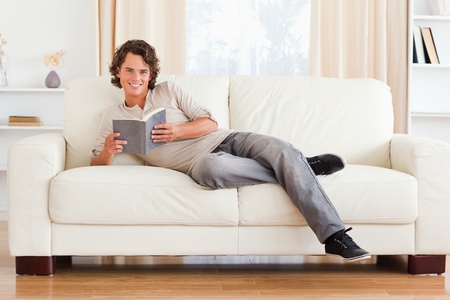 Man holding a book in his living room photo