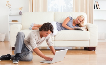 Man using a laptop while his girlfriend is holding a book in their living room photo