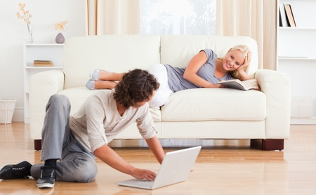 Man with a laptop while his girlfriend is holding a book in their living room photo