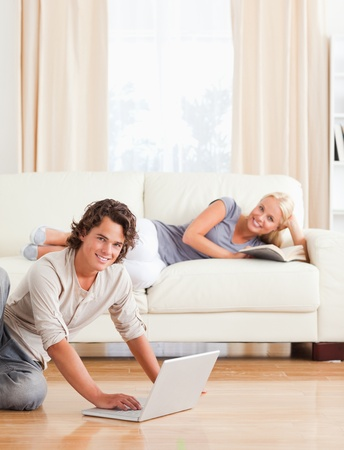 Portrait of a man with a notebook while his girlfriend is with a book in their living room photo