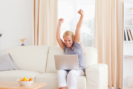 Cheerful blonde woman using a laptop in her living room photo
