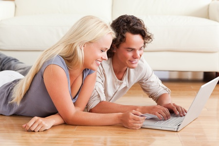 Young couple shopping online while lying on the floor photo