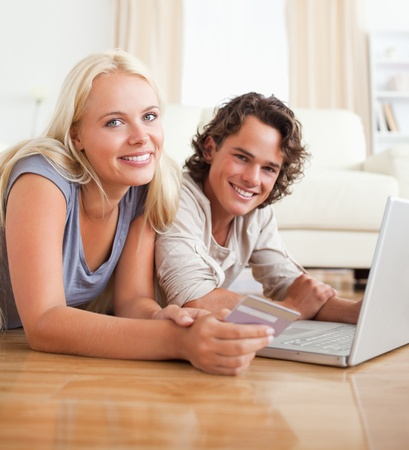 Cute couple booking their holidays online in their living room photo