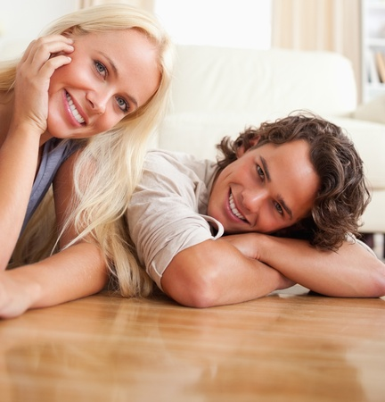 Close up of a couple lying on the floor looking at the camera photo