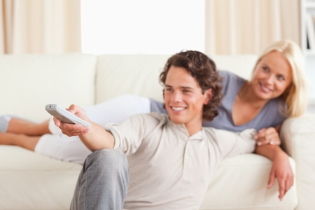 Smiling young couple watching TV in their living room photo