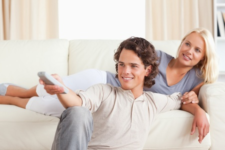 Cute young couple watching TV in their living room photo