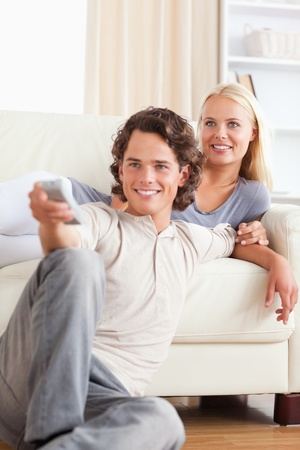 Portrait of a cute couple watching the television in their living room photo