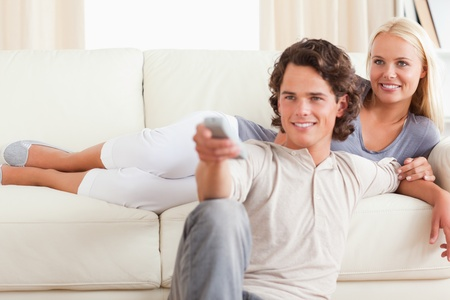 Cute couple watching the television in their living room photo