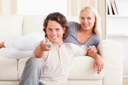 Lovely couple watching the television in their living room photo