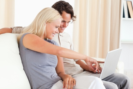 Woman pointing at something to her fiance on a screen in their living room photo
