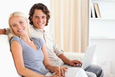 Couple with a notebook in their living room Stock Photo - 11192116