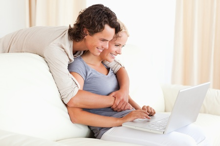 Lovely young couple using a notebook in their living room Stock Photo - 11232386