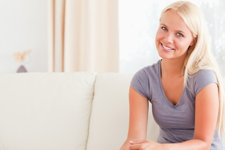 Blonde woman sitting on her sofa while looking at the camera Stock Photo - 11231506
