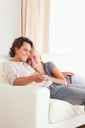 Portrait of a cute couple cuddling while watching TV in their living room photo