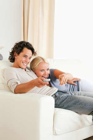 Portrait of a laughing couple cuddling while watching TV in their living room photo