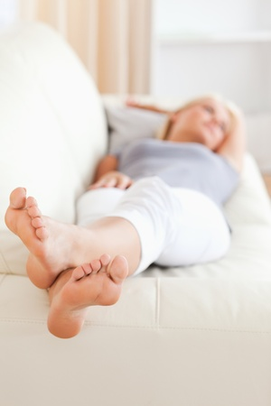 Woman lying on a sofa with the camera focus on her feet photo