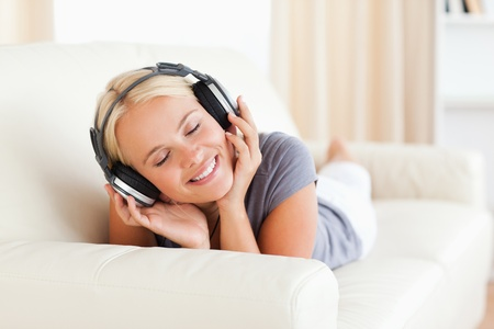 Woman enjoying some music in her living room photo