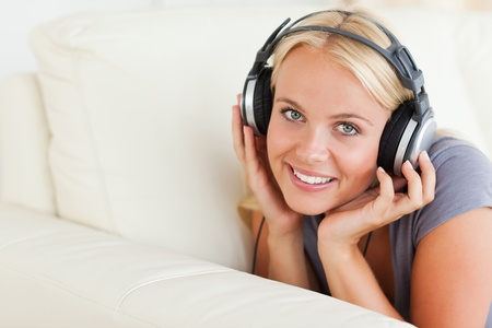 Blonde woman enjoying some music while looking at the camera photo