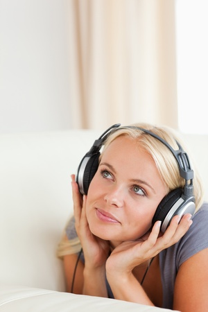 Portrait of a blonde woman enjoying some music in her living room photo