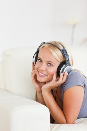 Portrait of a blonde woman listening to music in her living room photo