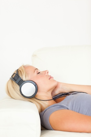 Portrait of a delighted woman listening to music in living room photo