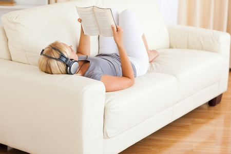 Woman listenning to music while reading a book in her living room photo