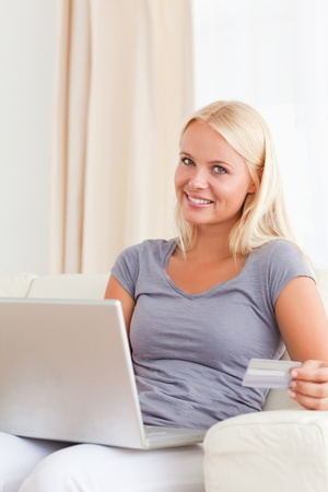 Portrait of a blonde woman shopping online in her living room photo