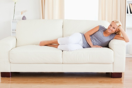 Blonde woman resting on a sofa while looking at the camera photo