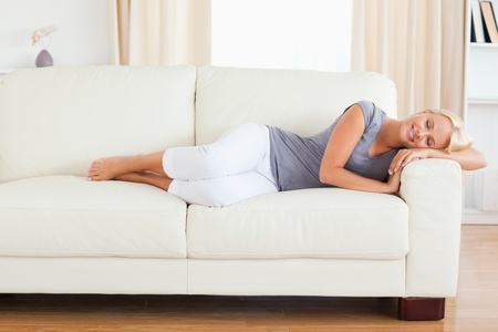 Calm woman resting on a sofa with her eyes closed photo
