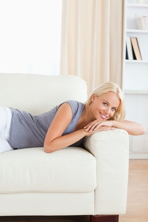 Portrait of a smiling woman lying on a sofa while looking at the camera photo