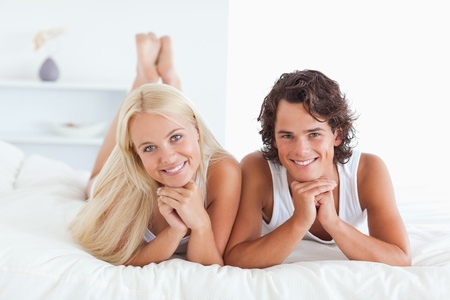 blonde couple: Couple lying on a bed looking at the camera Stock Photo