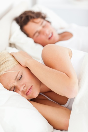 Portrait of a woman awaken by her boyfriends snoring in their bedroom photo
