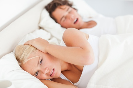 Angry woman awaken by her boyfriends snoring in their bedroom photo