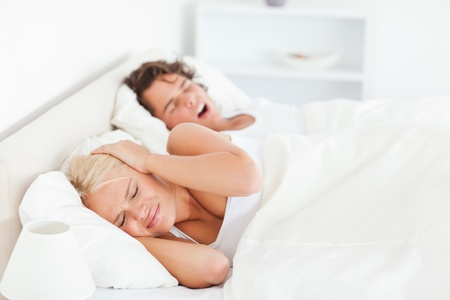 Annoyed woman awaken by her boyfriends snoring in their bedroom photo