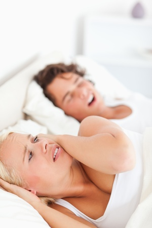 Portrait of an annoyed woman awaken by her fiance's snoring in their bedroom photo