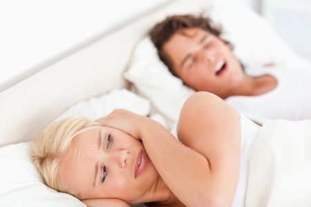 Annoyed woman awaken by her fiance's snoring in their bedroom photo