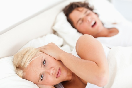 Angry woman awaken by her fiances snoring in their bedroom photo