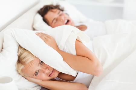 Woman awaken by her husbands snoring in their bedroom photo
