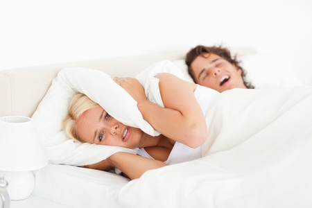 Angry woman awaken by her husbands snoring in their bedroom photo