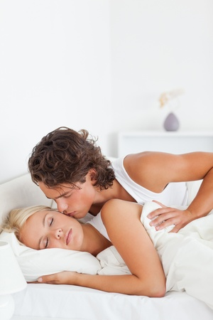 Portrait of a man kissing his fiance in their bedroom Stock Photo - 11192091