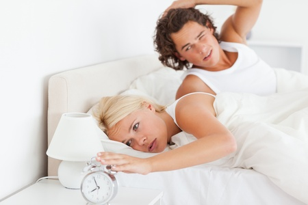 Tired couple waking up in their bedroom photo