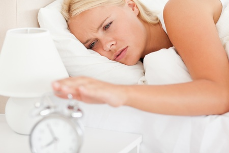 Woman awaken by an alarmclock in her bedroom photo