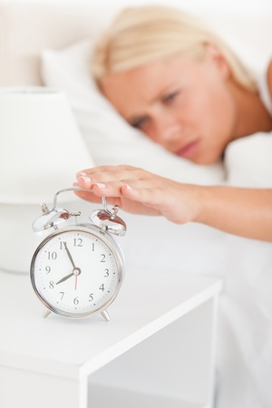 Portrait of a blonde woman awaken by an alarmclock with the camera focus on the object photo