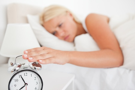 Woman switching off her alarmclock in her bedroom Stock Photo - 11231283