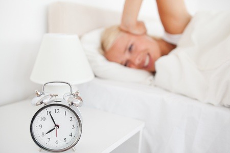 Angry woman awaken by her alarnclock in her bedroom Stock Photo - 11225792