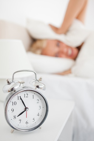 Portrait of a woman hidding her head in a pillow while the alarmclock is ringing in her bedroom Stock Photo - 11232749