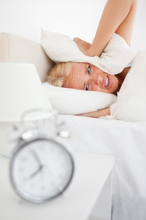 Portrait of a tired woman hidding her head in a pillow while the alarmclock is ringing in her bedroom Stock Photo - 11232982