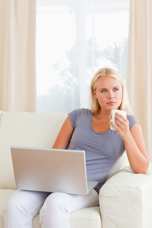 Portrait of woman having a tea while holding a laptop in her living room Stock Photo - 11232835